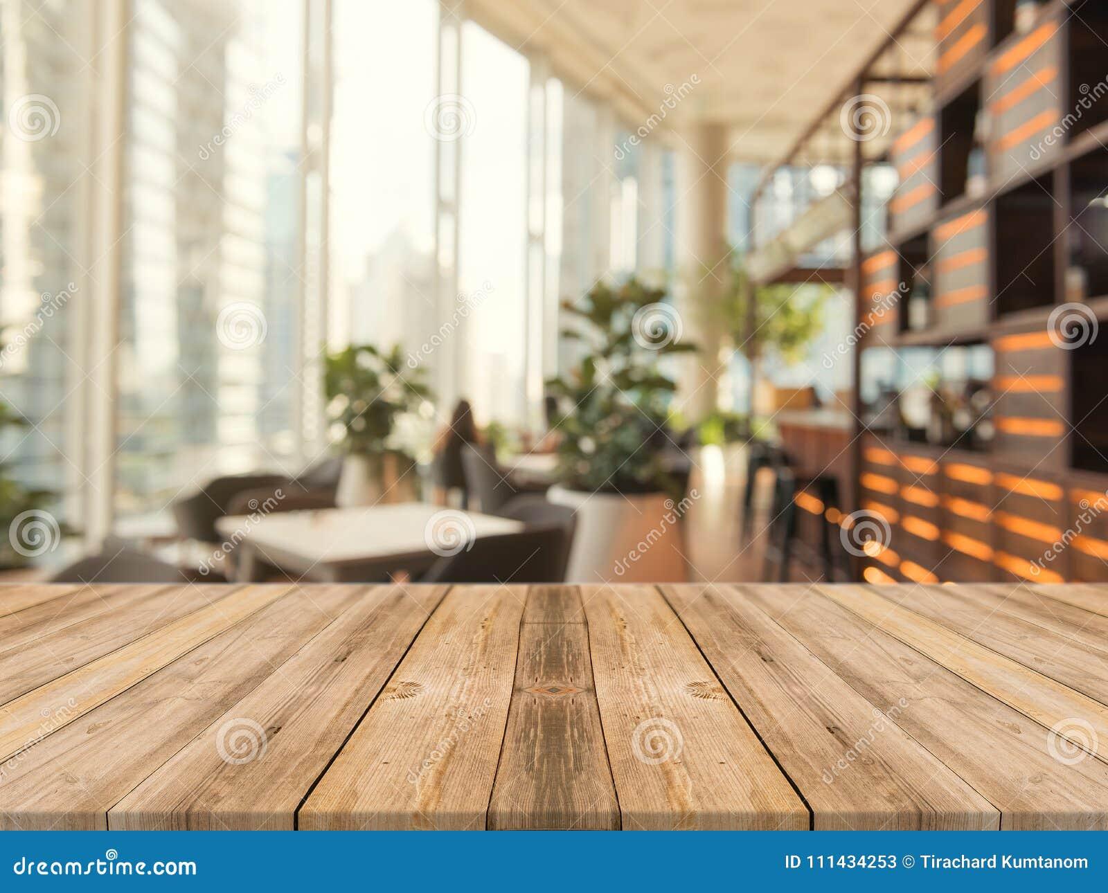 Drewnianej deski pusty stołowy wierzchołek dalej zamazany tło Perspektywiczny brown drewno stół nad plamą w sklep z kawą tle
