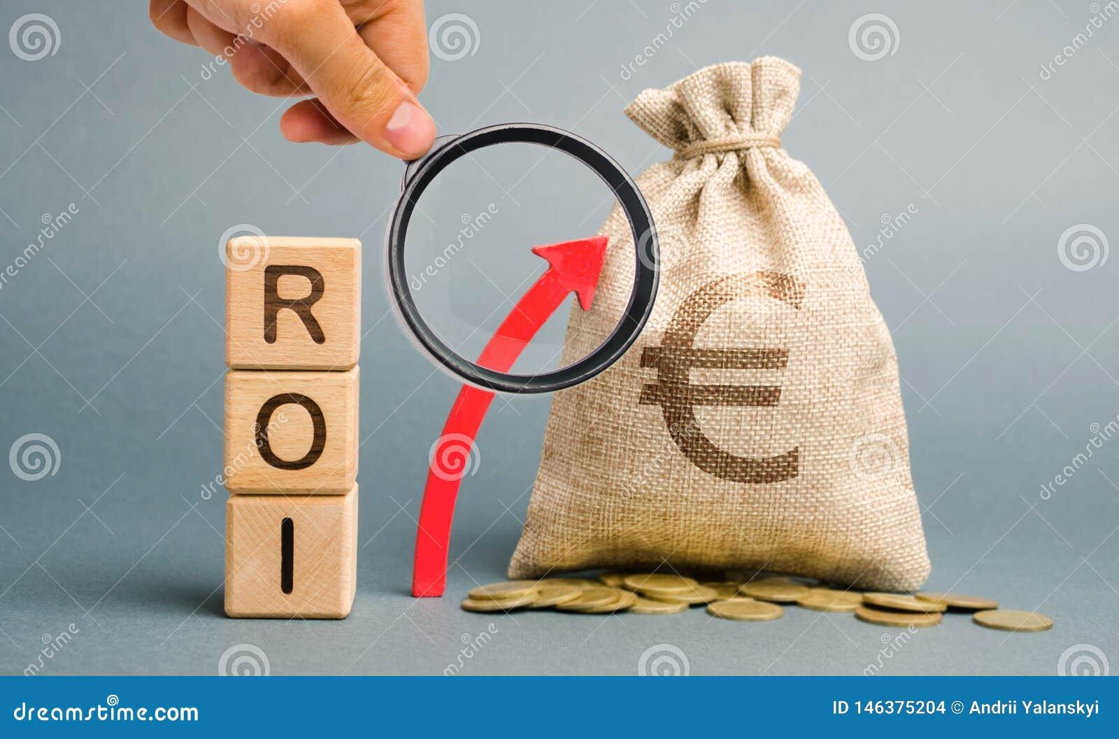 Drewniani bloki z słowem ROI i w górę strzały z pieniądze torbą Wysoki poziom biznesowa dochodowość Wskaźnik rentowności,