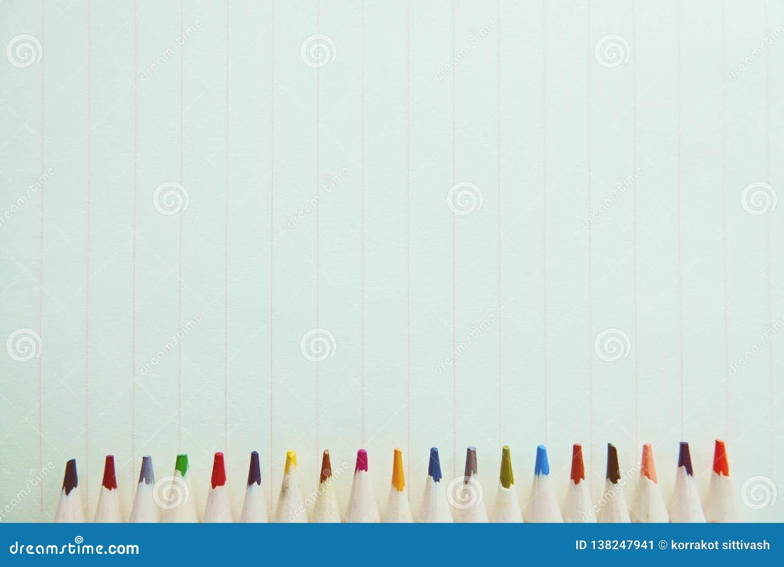 Drewniani kolorowi ołówki na notatniku tapetują tło