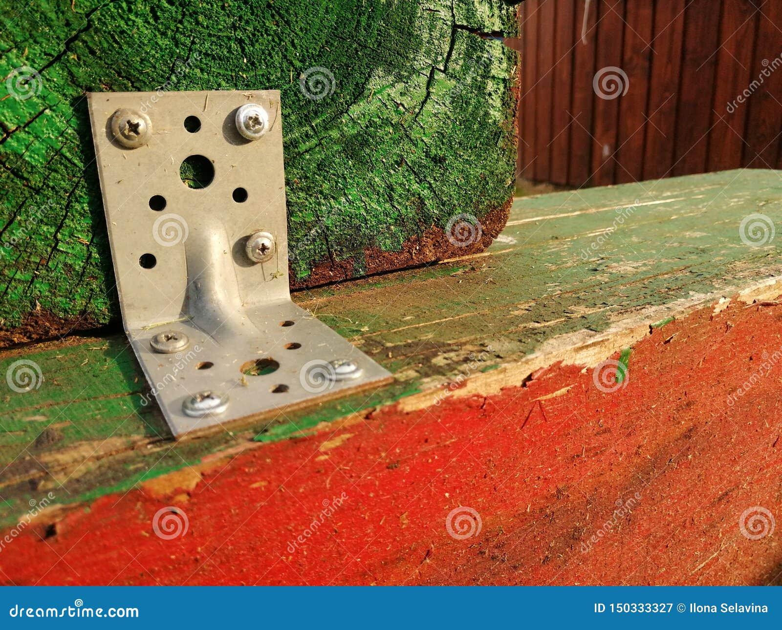 Drewniani opóźnienia przymocowywają wpólnie malujących zielonych i czerwonych budynków elementy