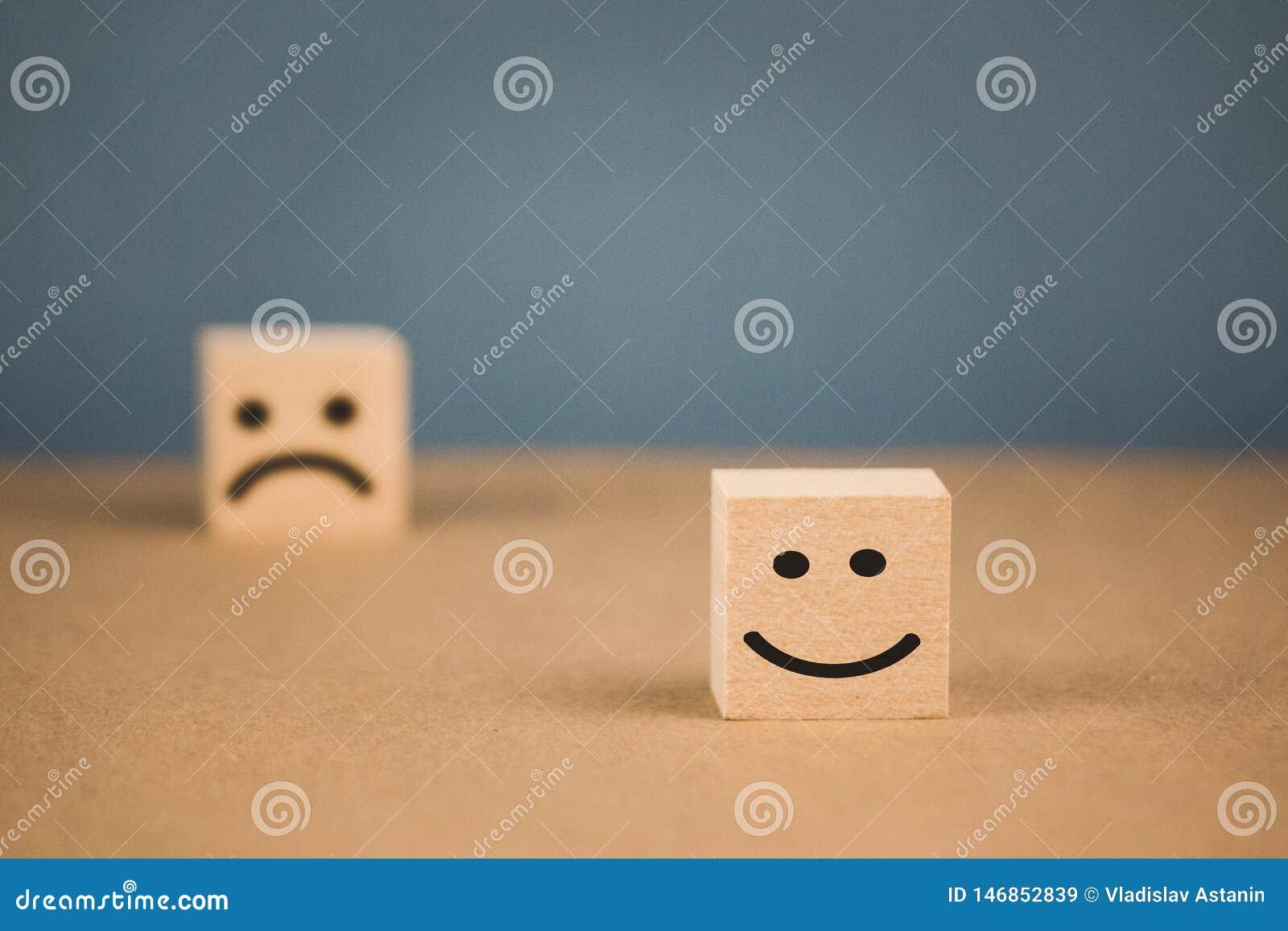 Drewniani sześciany z uśmiechniętymi emoticons i smutnym jeden