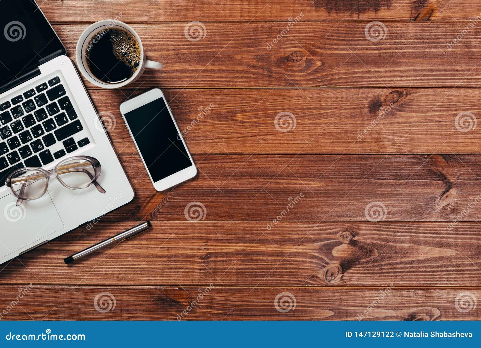 Drewniany biurowego biurka st?? z laptopem, fili?anka kawy i dostawami,