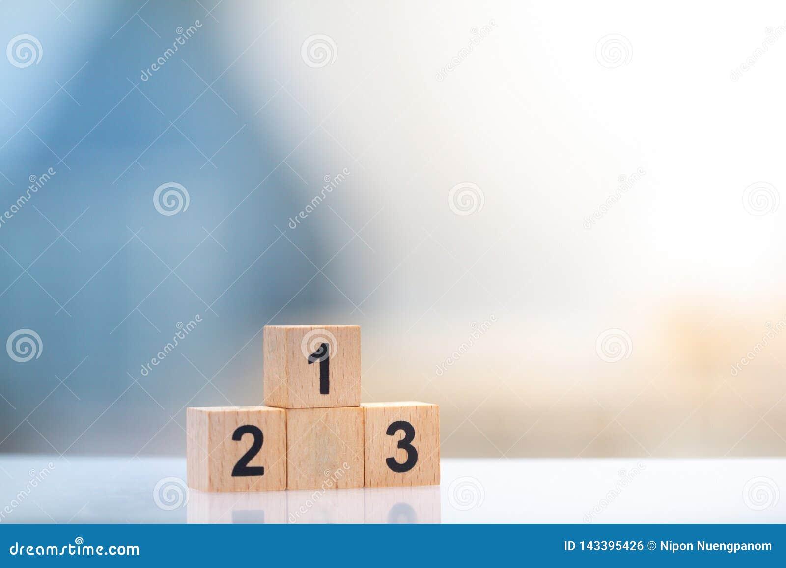 Drewniany blokowy zwycięzcy podium najpierw, drugi, i na trzecim miejscu na pejzażu miejskiego tle