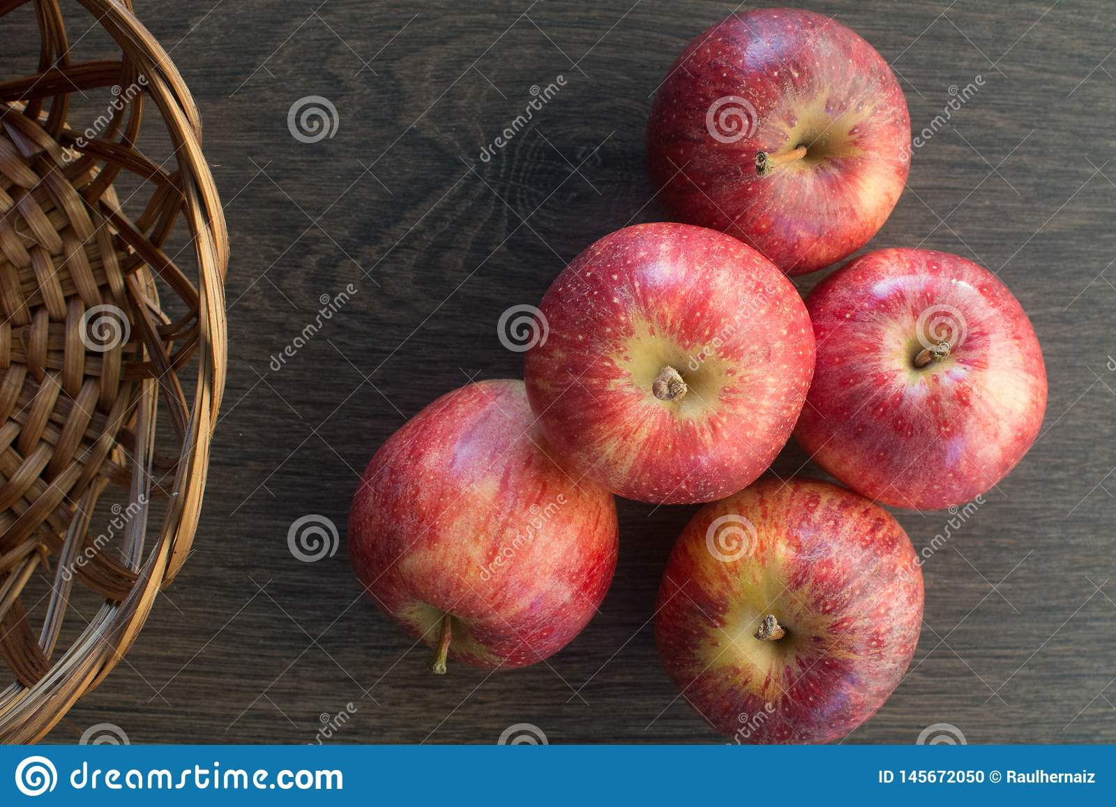 Drewniany ciemny t?o Czerwoni jabłka na drewnianym tle w koszu tworzy starą i nieociosaną atmosferę, Przedstawicielstwo