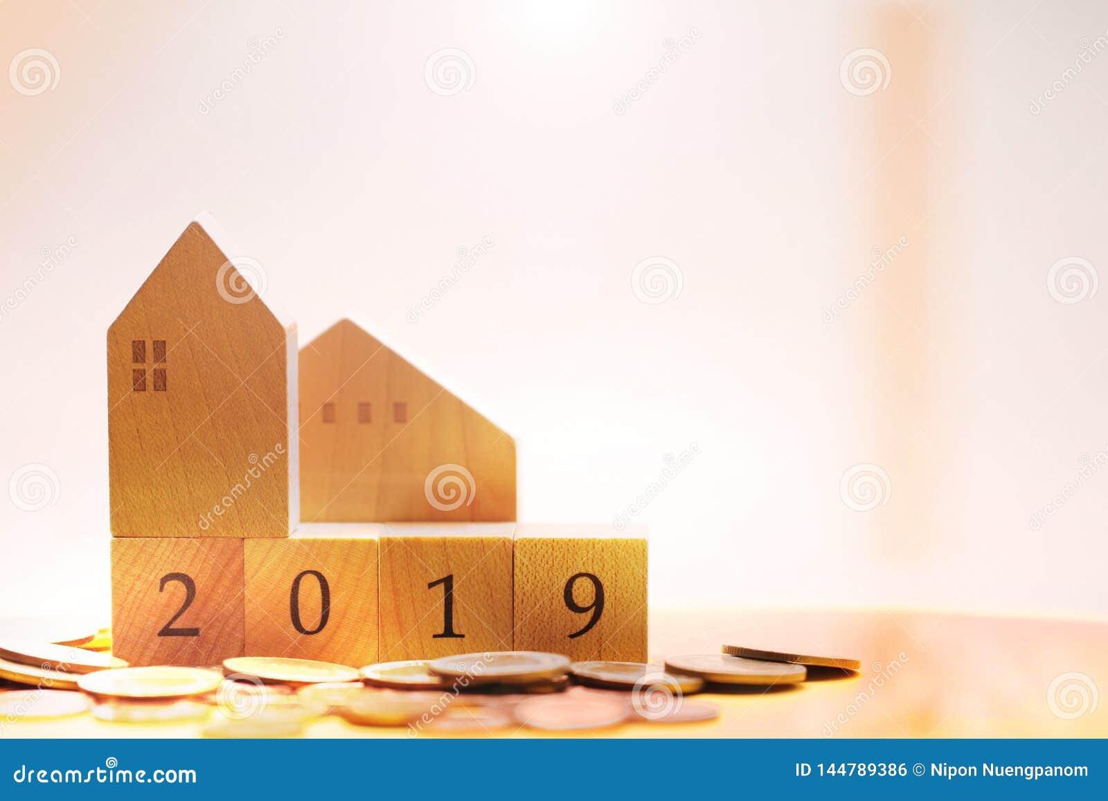 Drewniany dom z blokowymi liczbami roku 2019 otaczanie stosem monety