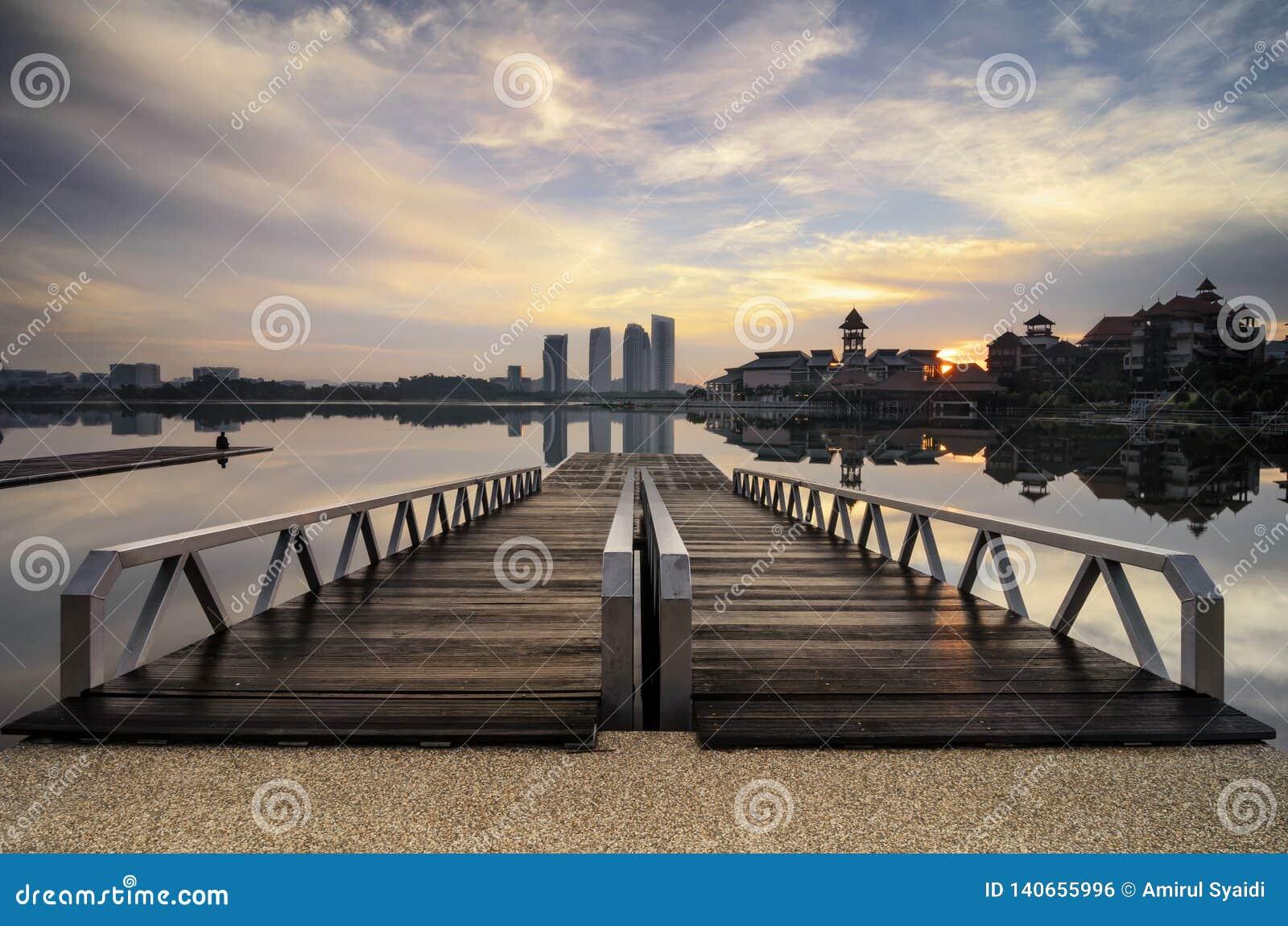Drewniany jetty i piękna sceneria lakeshore wschodu słońca tło