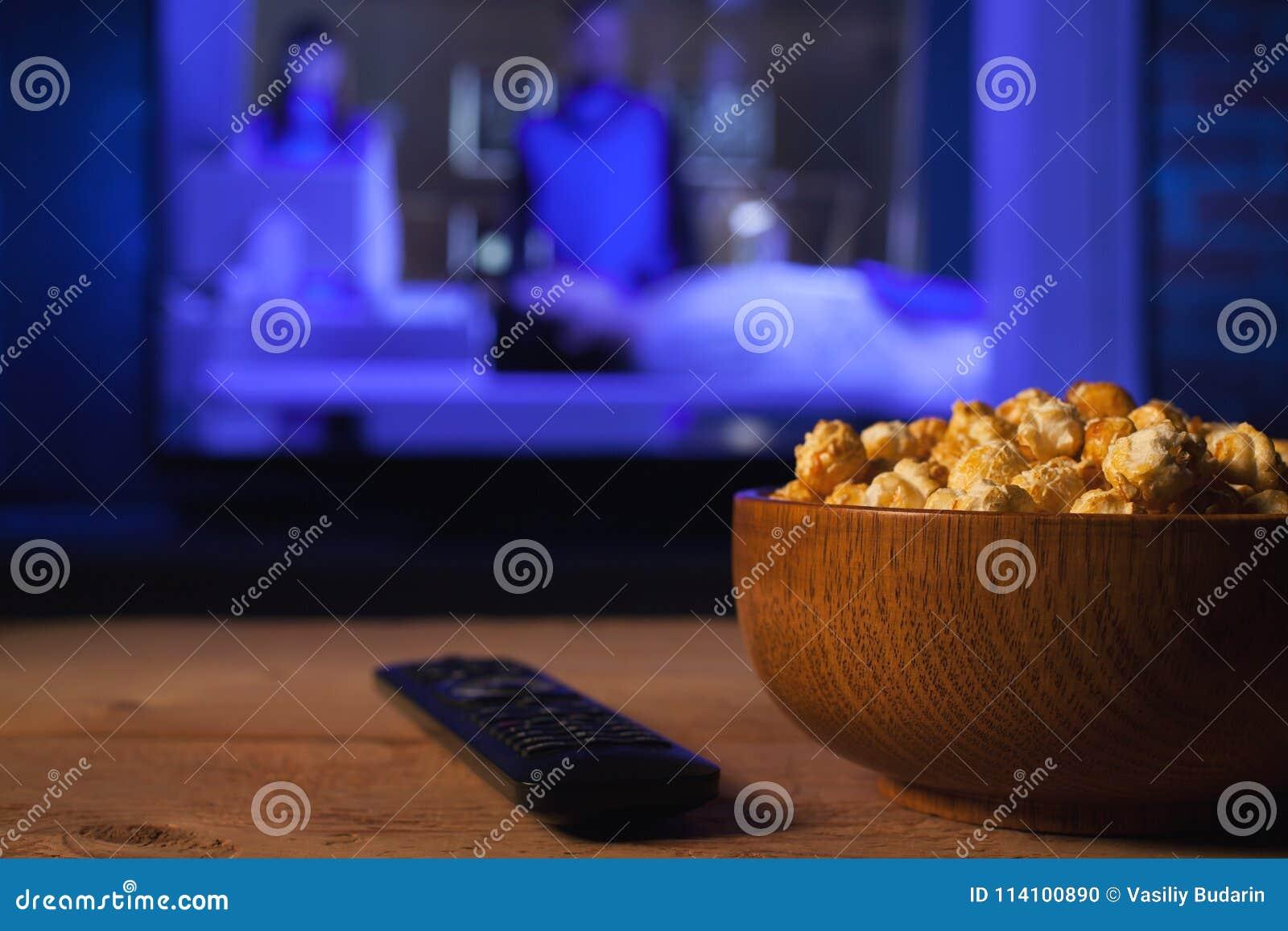 Drewniany puchar popkorn i pilot do tv w tle TV pracuje Evening wygodnego dopatrywanie w domu film lub seriale telewizyjni