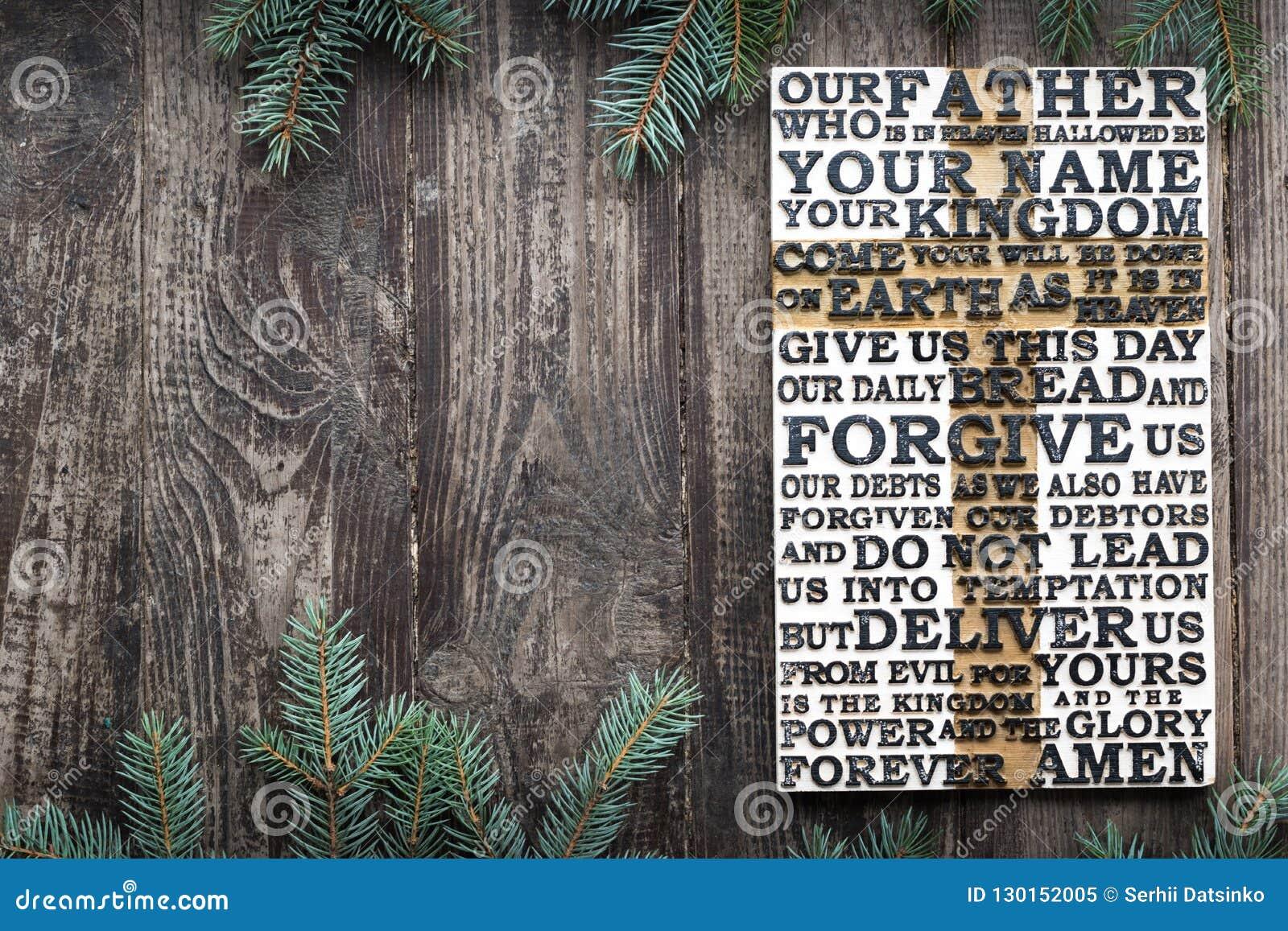 Drewniany rzeźbiący słowo władyki modlitwa na starej wietrzejącej drewnianej desce z jedlinowym gałąź tłem