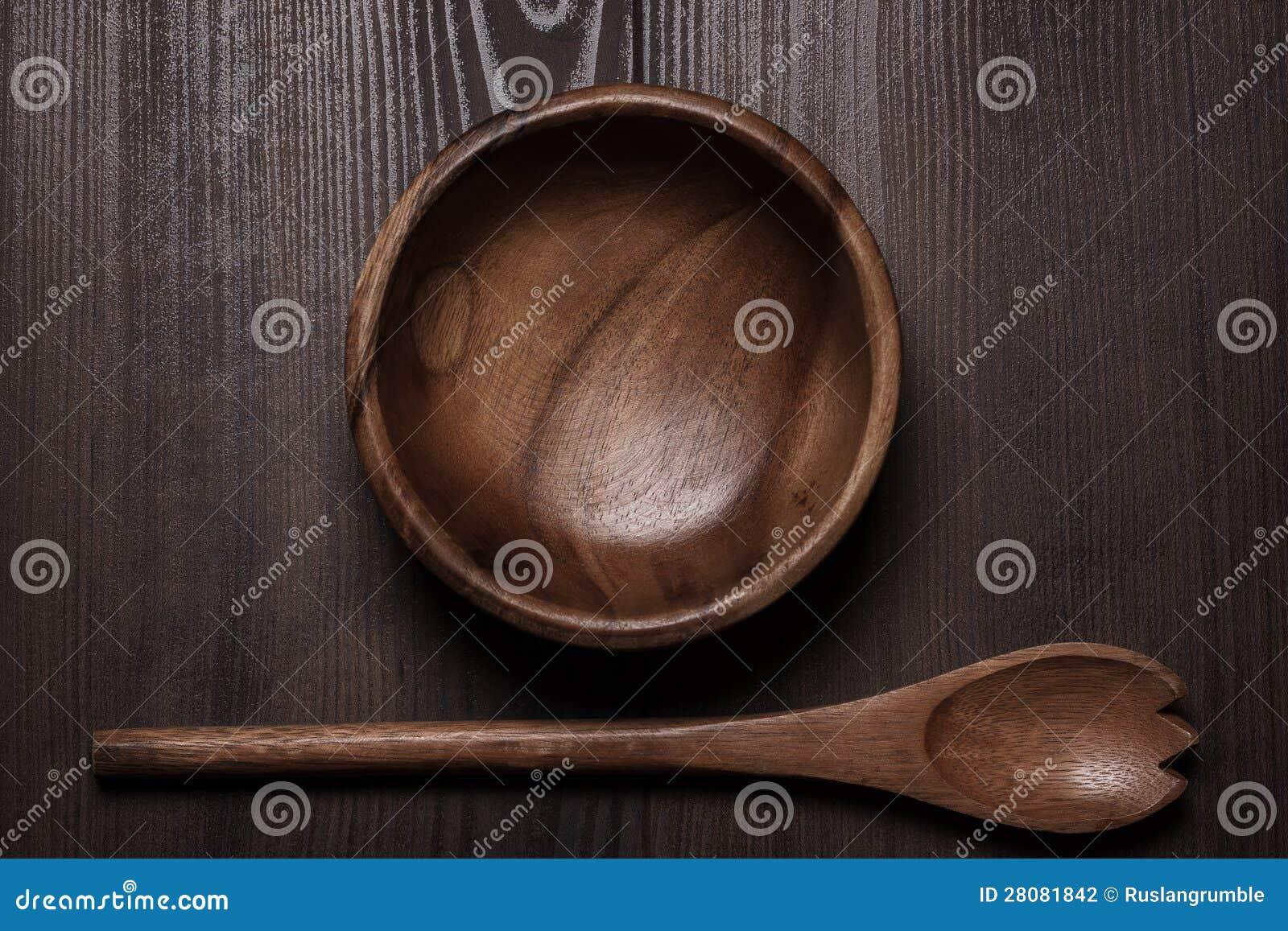 Drewniany sałatkowy puchar i łyżka na stole