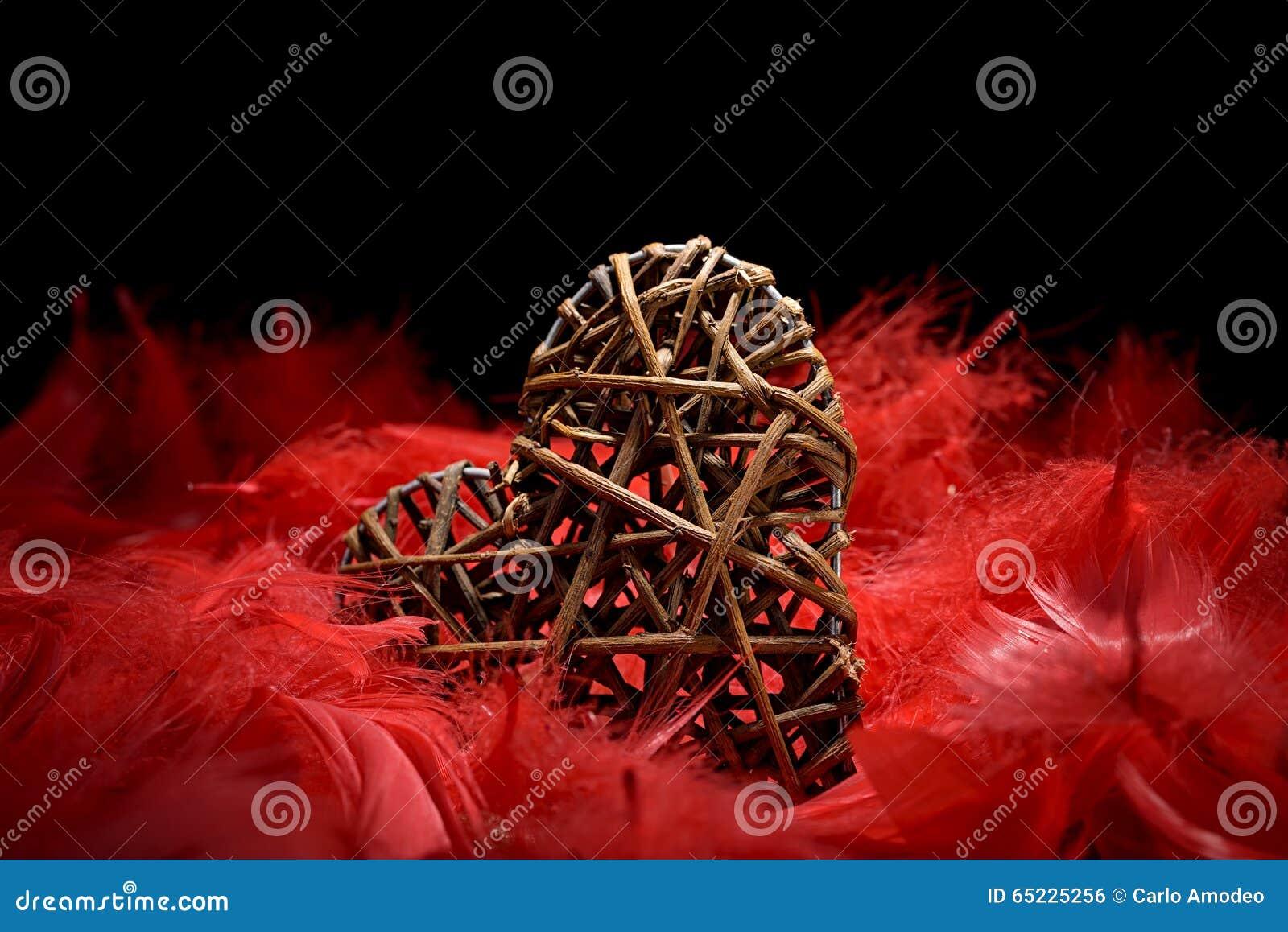 Drewniany serce w czerwonych piórkach