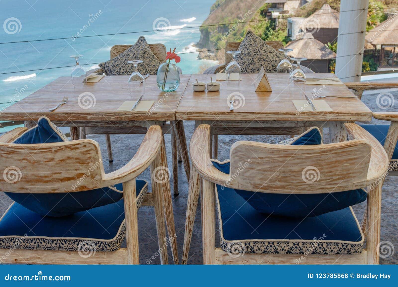 Drewniany stół i krzesła przy plenerową falezy kawiarnią