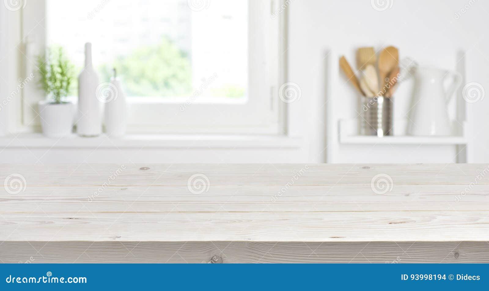 Drewniany stół na zamazanym tle kuchenny okno i półki