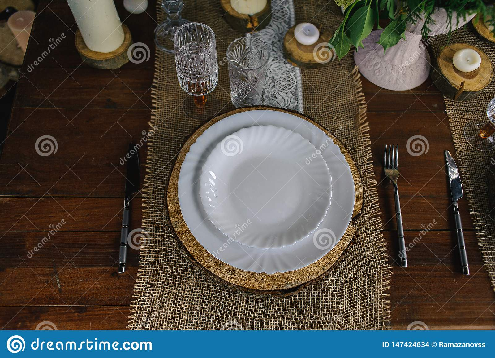 Drewniany stół ustawia z świeczkami, biel pieluchą, półkową i szarą