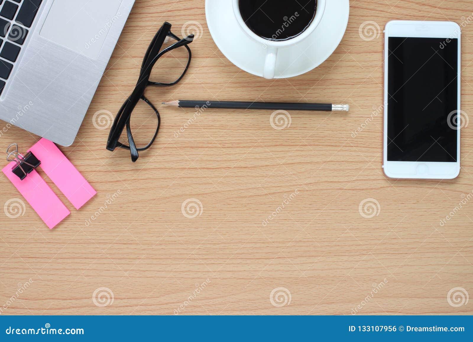 Drewniany stołowy działanie komputerowego i kawowego kubek blisko a