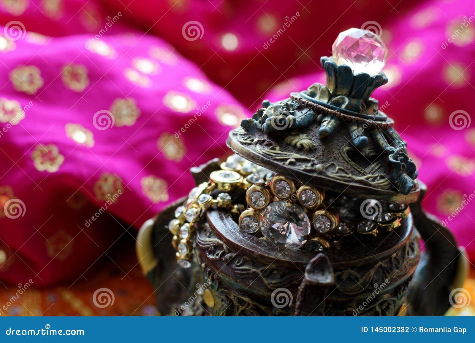 Drewniany szkatuły pudełko z orientalnymi wzorów słoniami pełno złocista biżuteria na Malinowym tkaniny tle