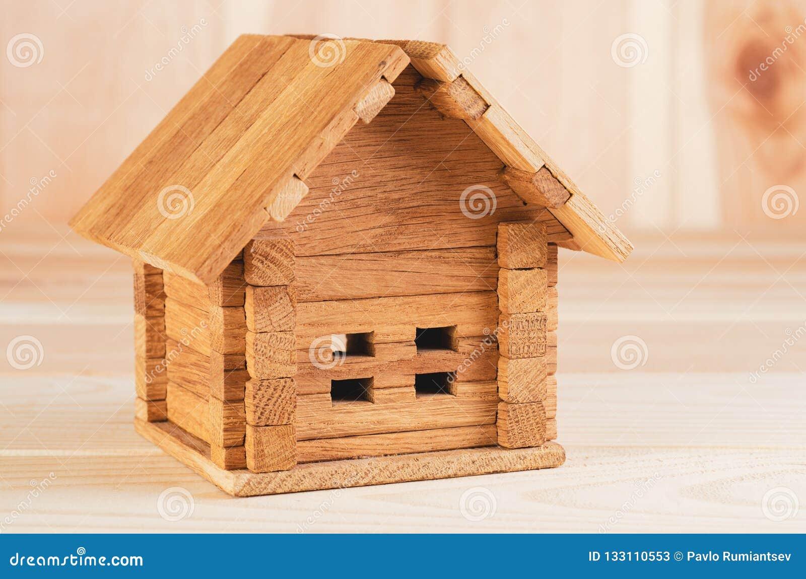 Drewniany zabawkarski falcowanie dom strzelał ampułę na drewnianym tle