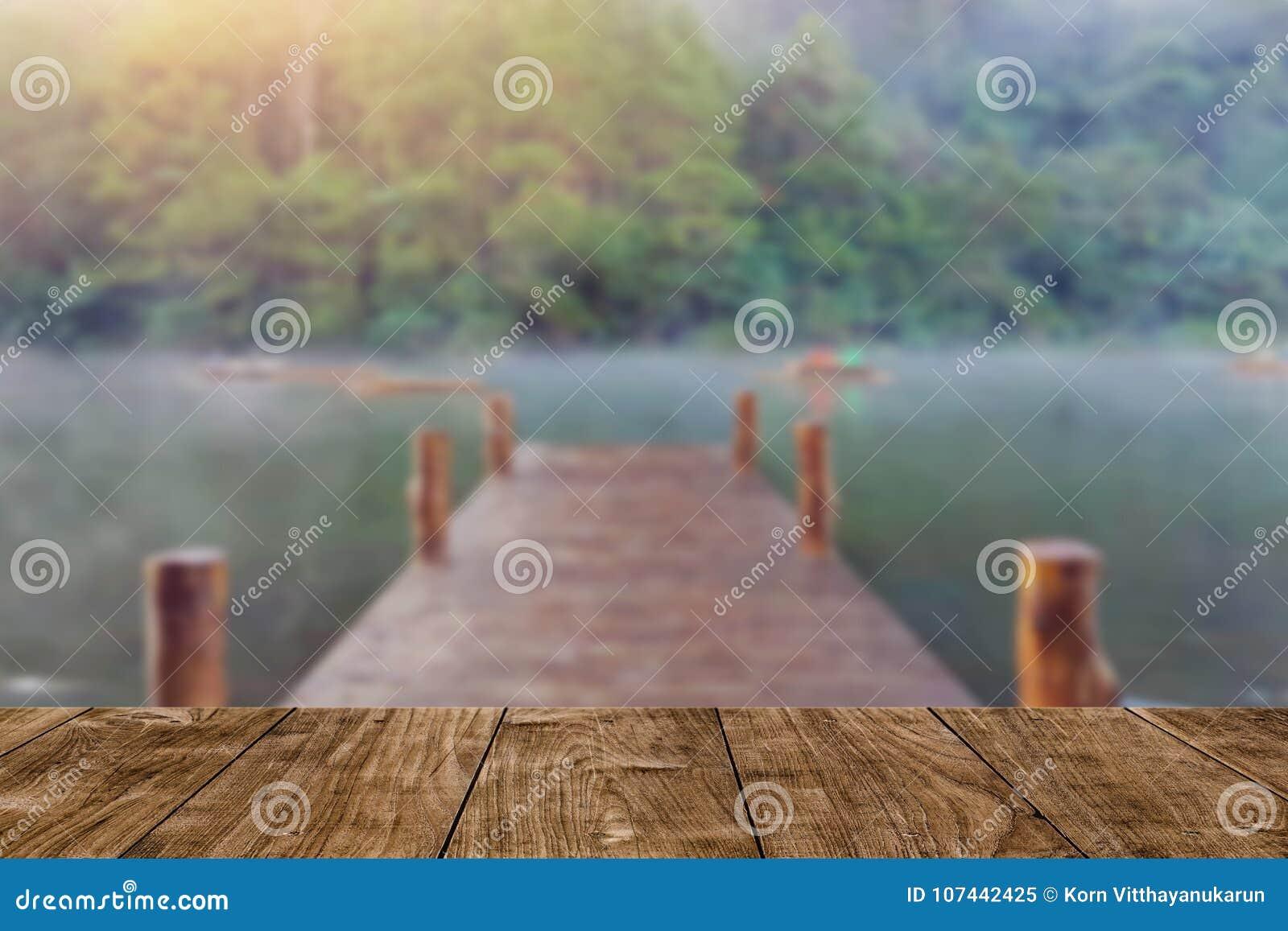 Drewno stół z plamy drewna mosta doku podróży jeziornym tłem