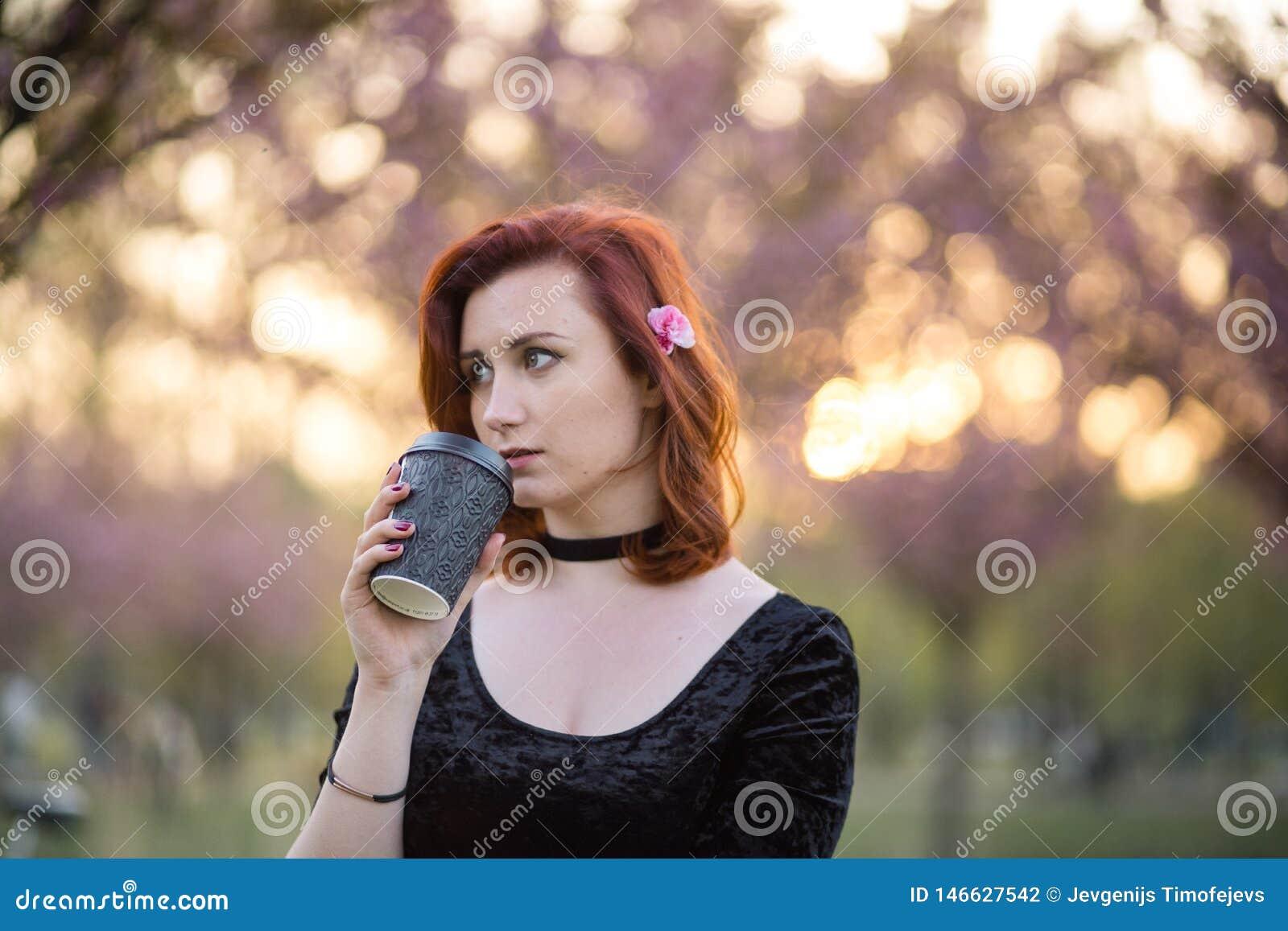 Dricka kaffe fr?n papper r?na koppen - den lyckliga unga loppdansarekvinnan som tycker om fri tid i sakura en k?rsb?rsr?d blomnin