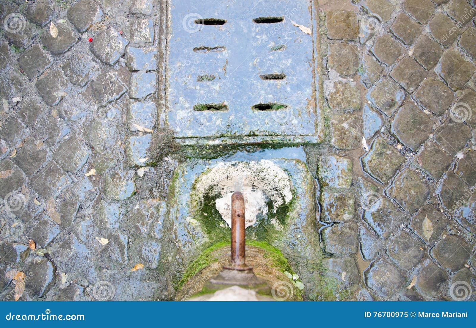 Drickbart springbrunnvatten i Rome med kullersten