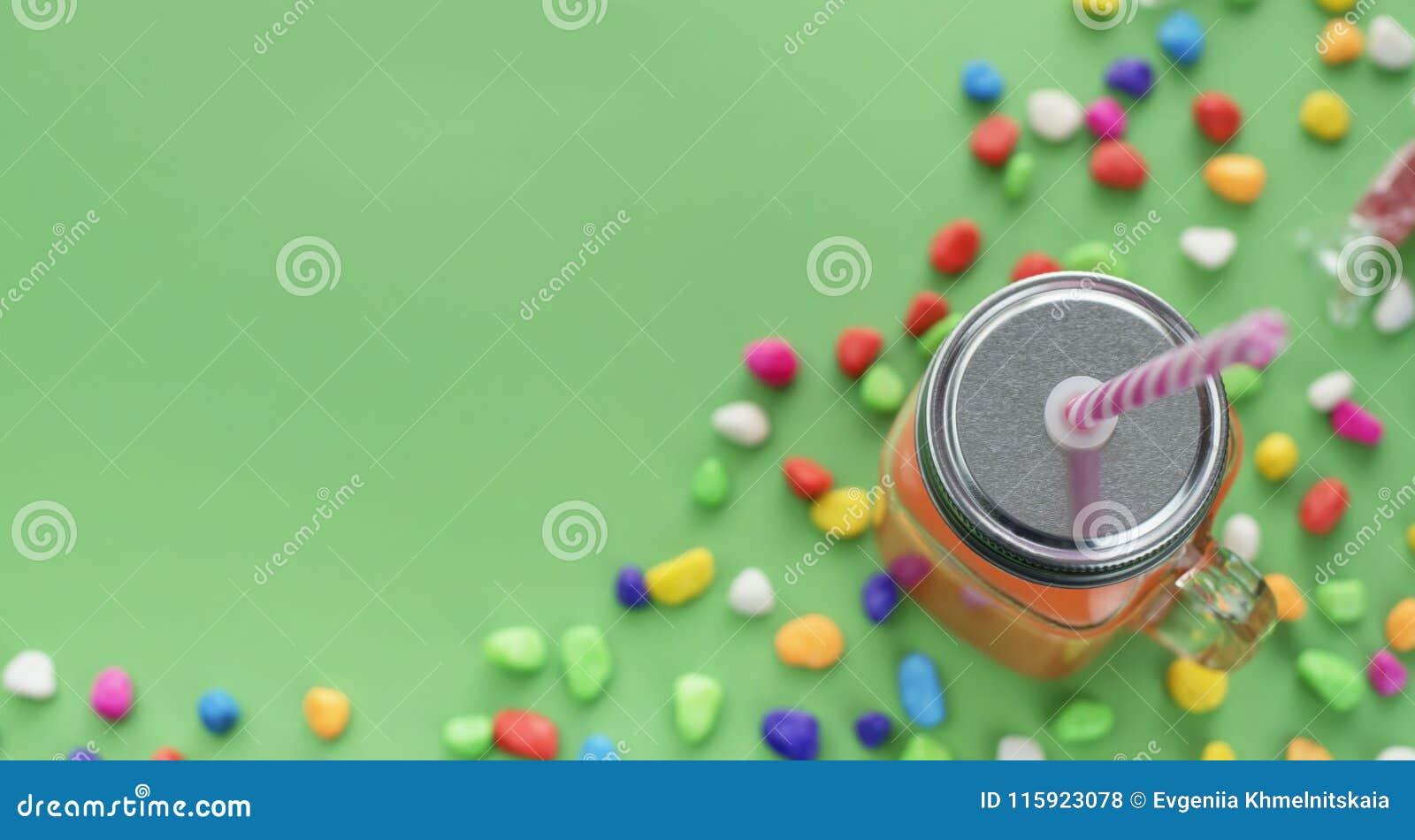 Dricker naturliga nya Smoothies för baner i den glass koppen med sugrör på grön bakgrund