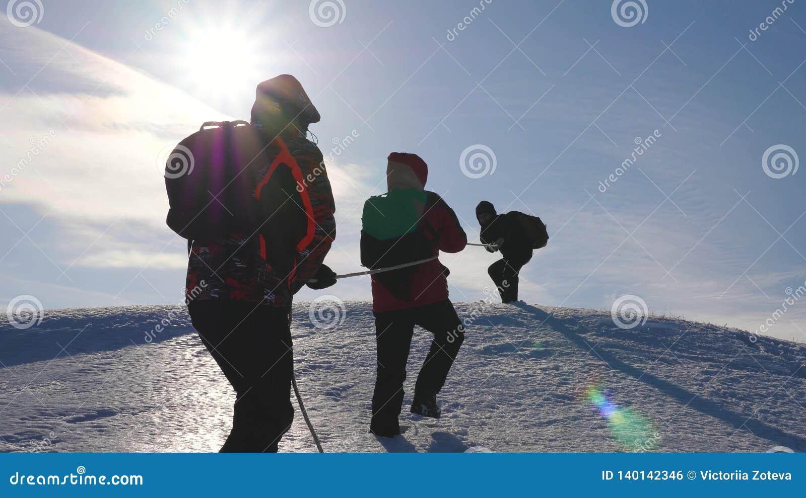 Drie Alpenists beklimmen kabel op sneeuwberg De toeristen werken samen als team schuddende hoogten die moeilijkheden overwinnen