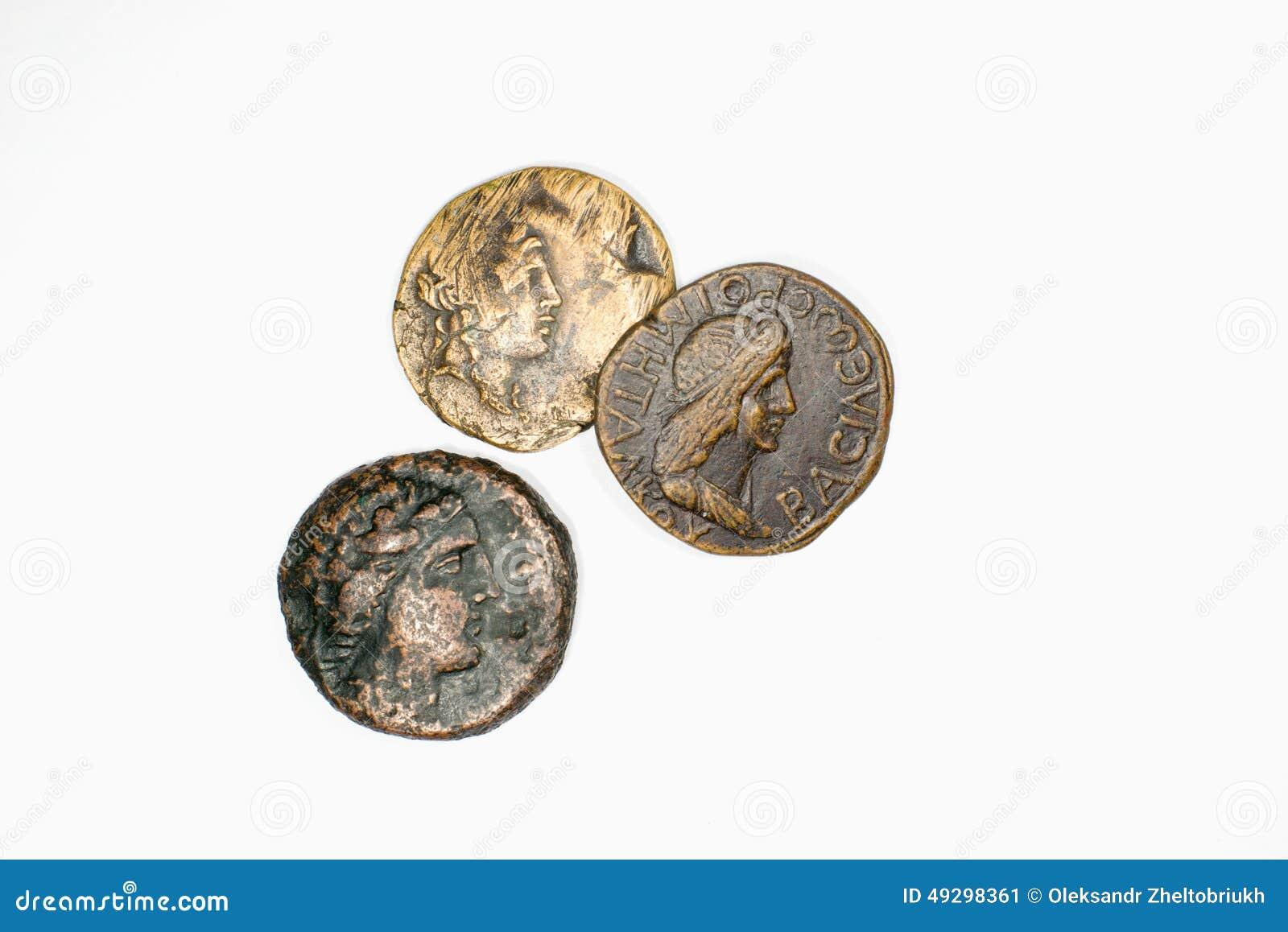 Drie antieke muntstukken met portretten op een witte achtergrond