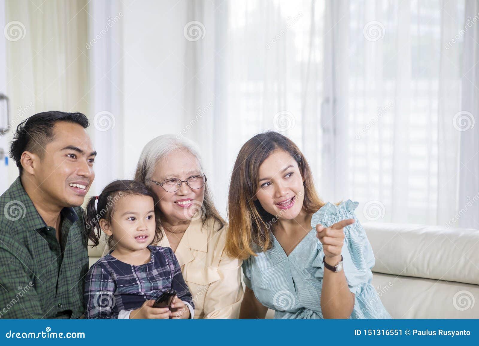 Drie Aziatische generatiefamilie die op TV thuis letten