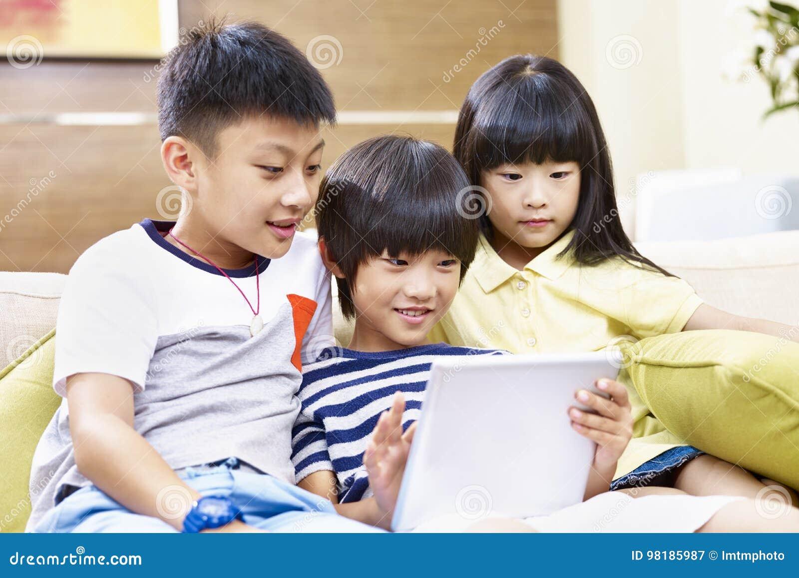 Drie Aziatische kinderen die digitale tablet samen gebruiken
