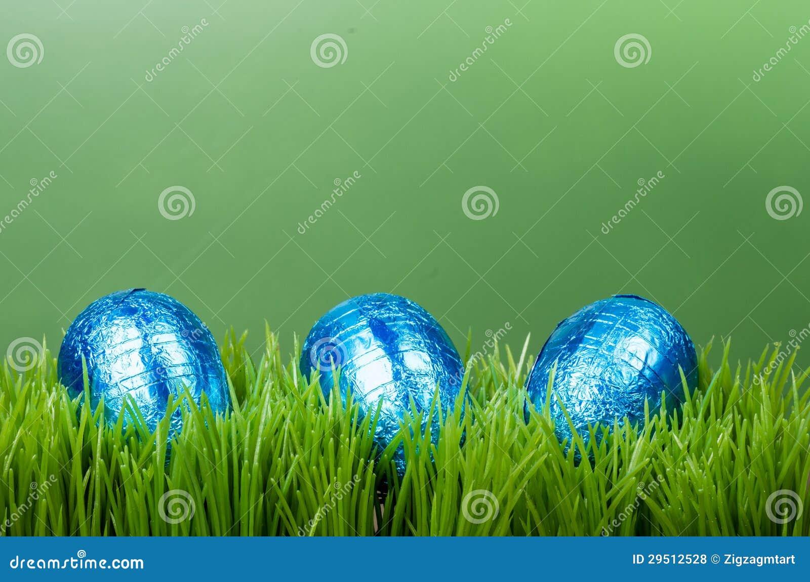 Drie blauwe foliePaaseieren op gras