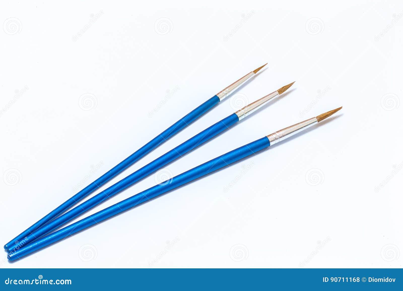 Drie blauwe verfborstels op een witte achtergrond Geïsoleerde