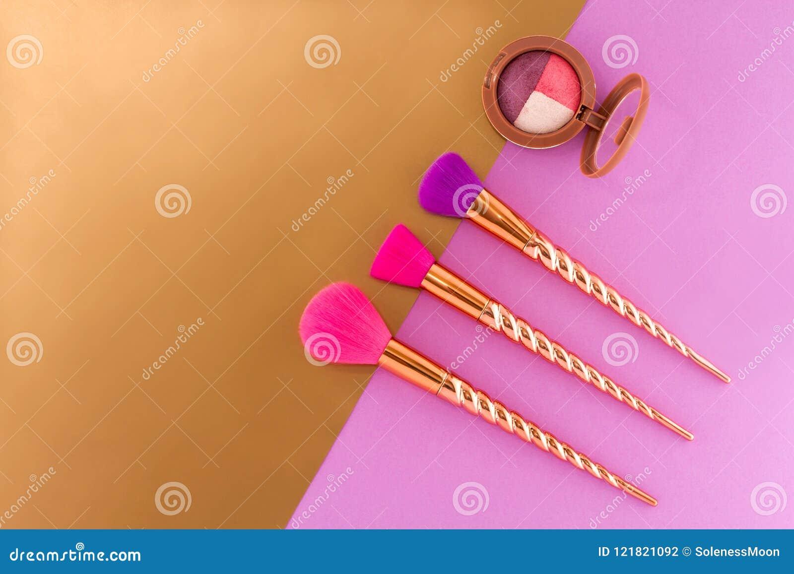 Drie borstels en oogschaduw op dubbele purple - koper-gouden achtergrond