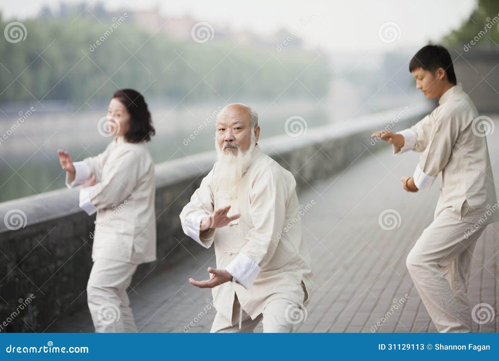 Drie Chinese Mensen die Tai Ji Outdoors uitoefenen
