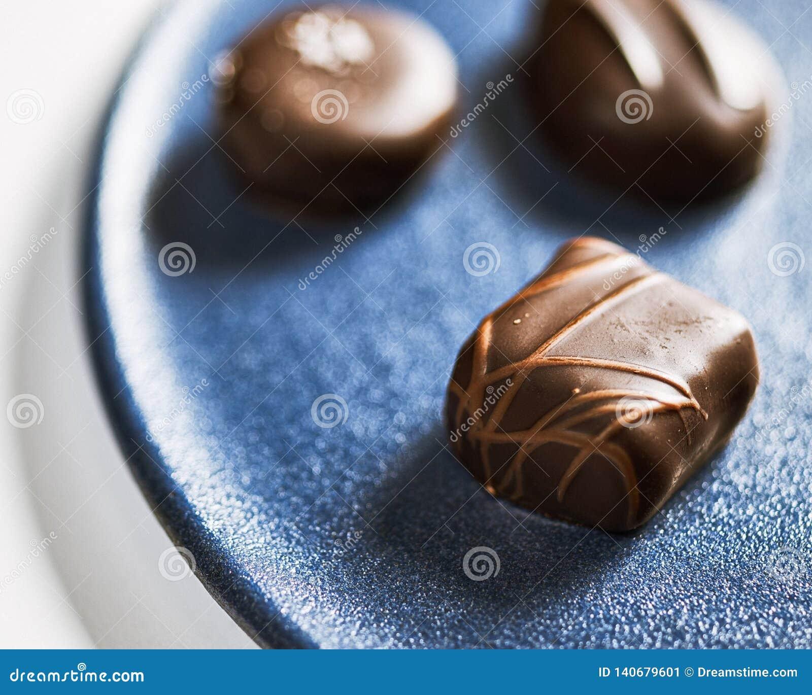 Drie Chocolade op een Blauwe Ceramische Plaat