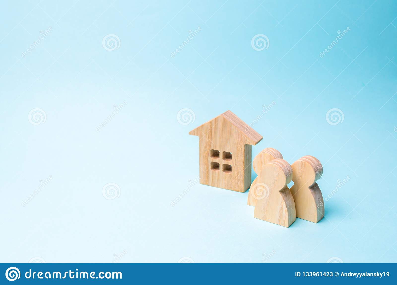 Drie cijfers van mensen en een blokhuis op een blauwe achtergrond Het concept betaalbare huisvesting en hypotheken voor het kopen