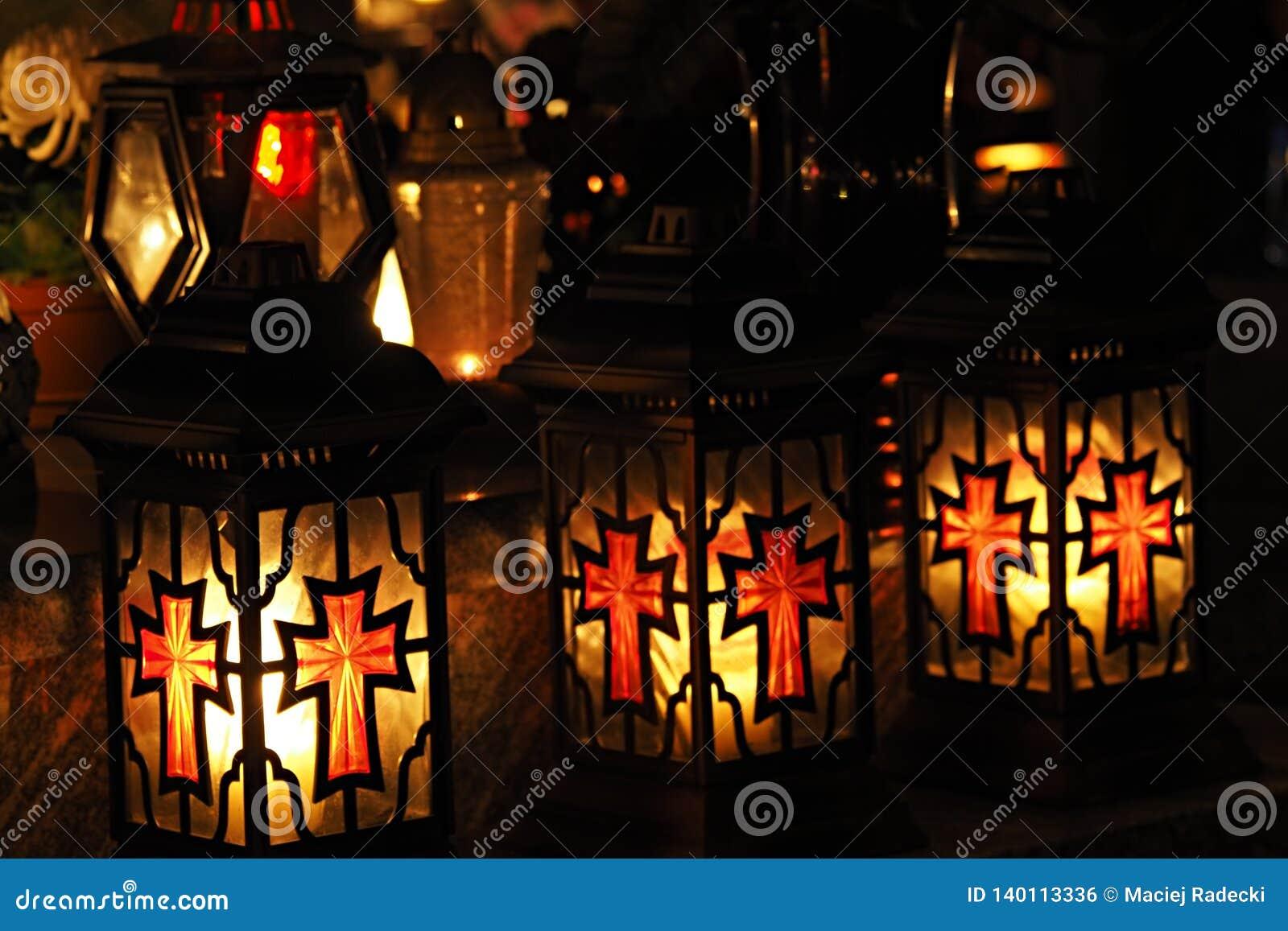 Drie gele en rode ernstige kaarsen in een begraafplaats bij nacht