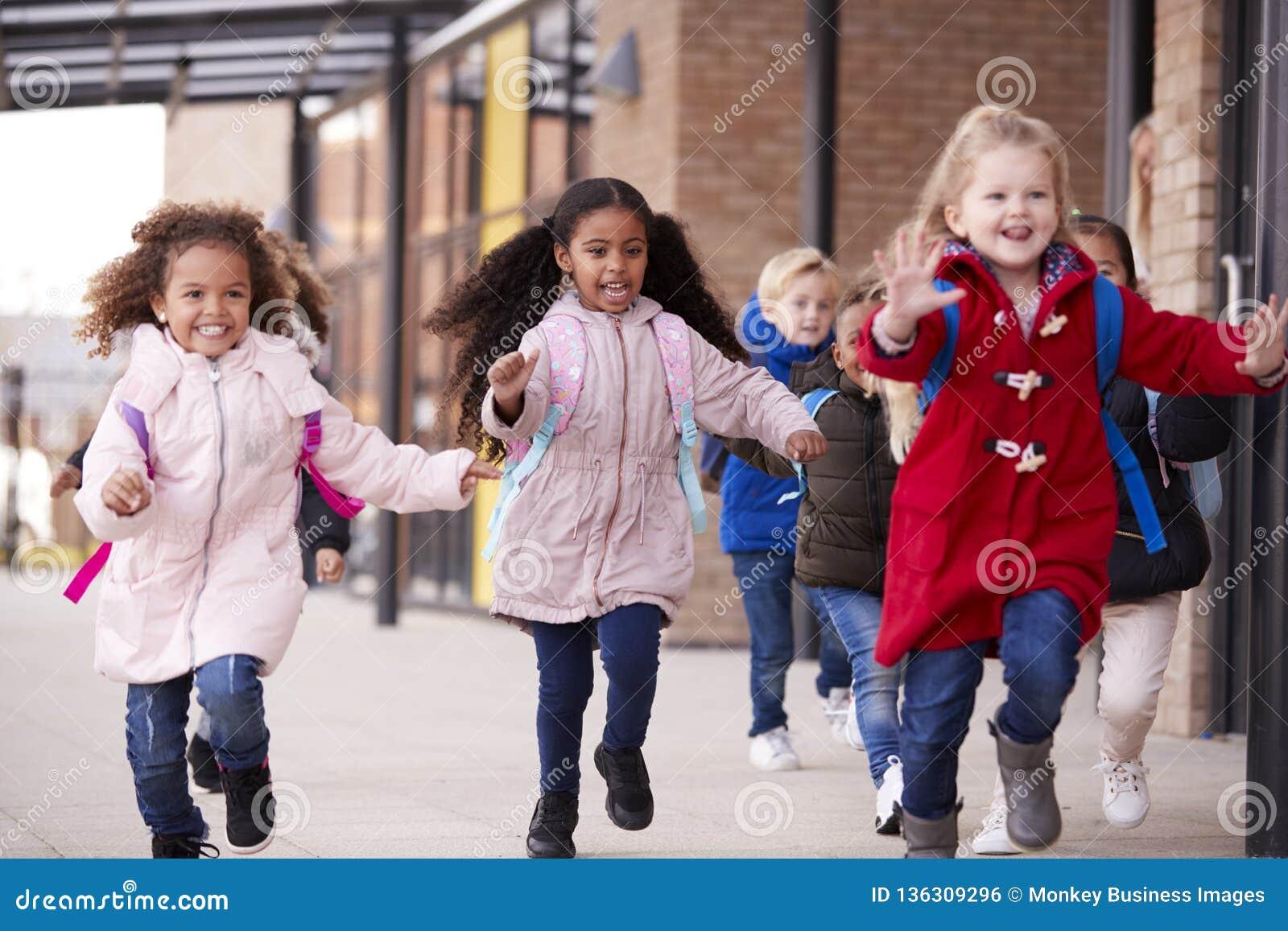 Drie gelukkige jonge schoolmeisjes die lagen dragen en schooltassen dragen die in een gang met hun klasgenoten buiten hun infa lo