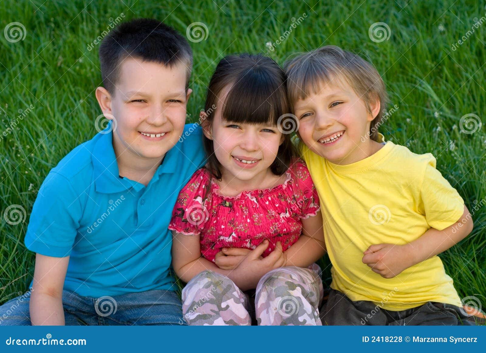 Drie gelukkige kinderen in gras