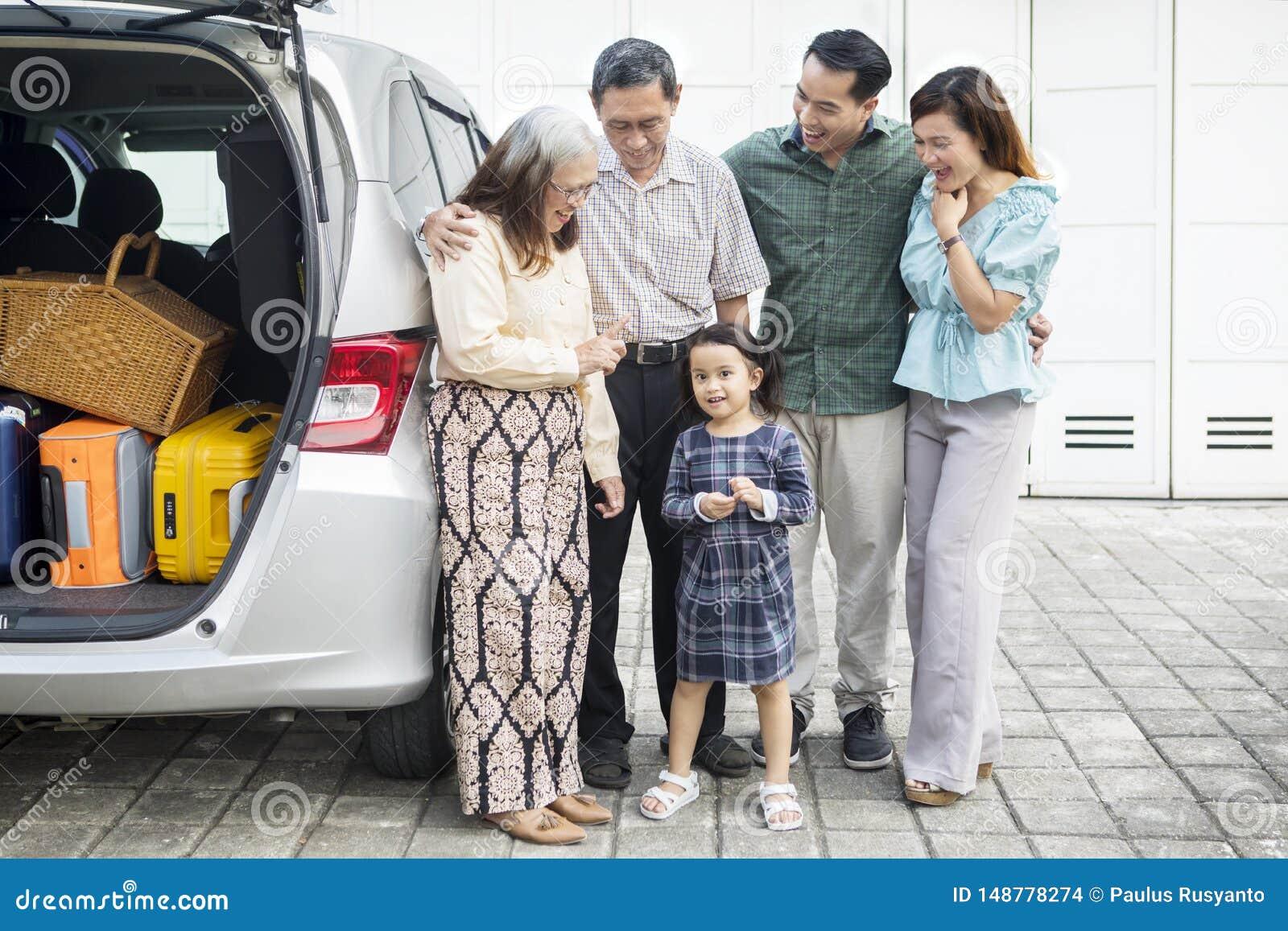 Drie generatiefamilie met auto in de garage