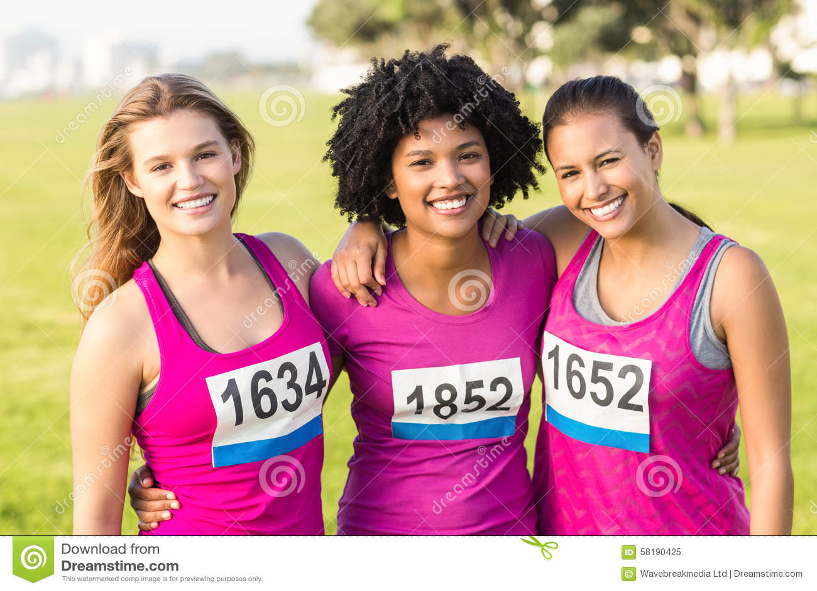 Drie glimlachende agenten ondersteunend de marathon van borstkanker
