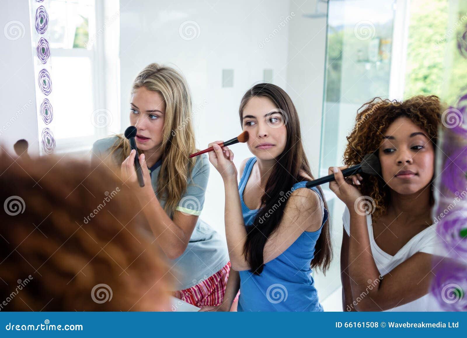 Drie glimlachende vrienden die make-up samenbrengen op