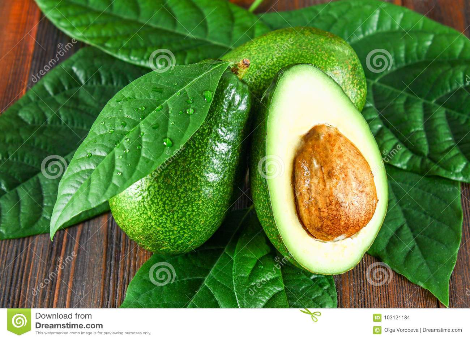 Drie groene ruwe rijpe avocadovruchten en een besnoeiing half met een been met bladeren op een bruine houten lijst