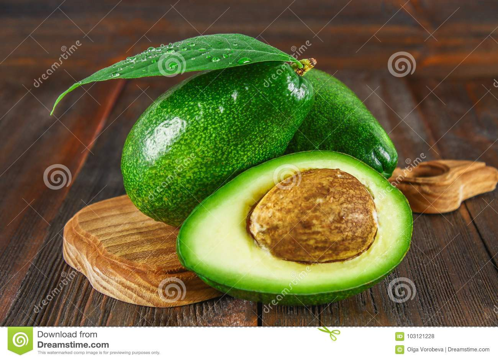 Drie groene ruwe rijpe avocadovruchten en een besnoeiing half met een been met bladeren op een houten scherpe raad op een bruine