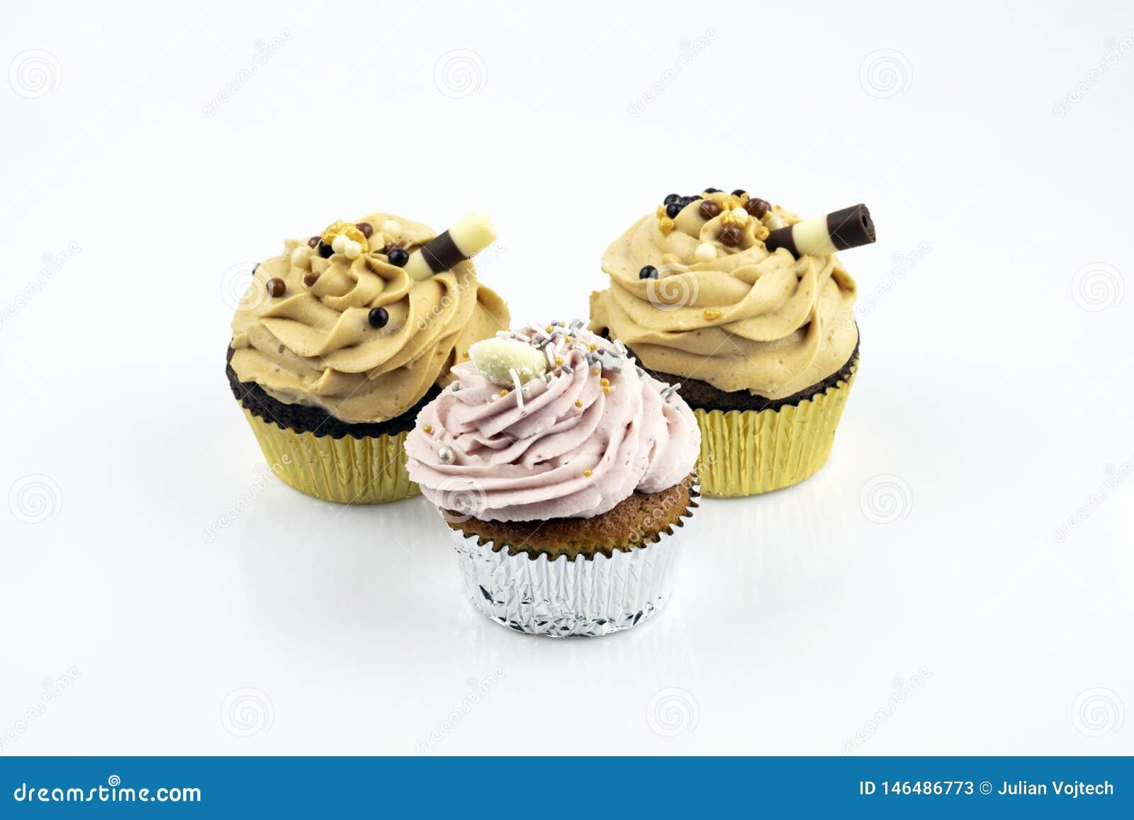 Drie grote en heerlijke die muffins met karamel en aardbeischuim worden gevuld Verfraaid met een zoete buis