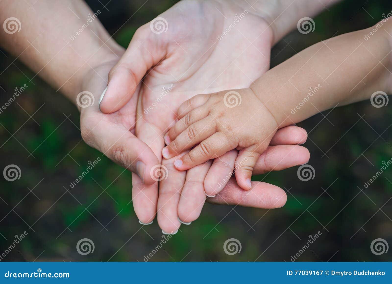 Drie handen van dezelfde familie - de vader, de moeder en de baby blijven samen Het concept familieeenheid, bescherming, steun