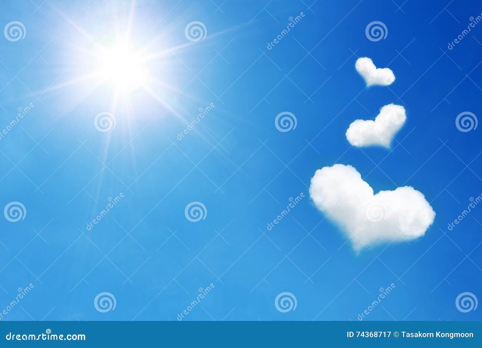 Drie hart gevormde wolk op blauwe hemel met zonneschijn