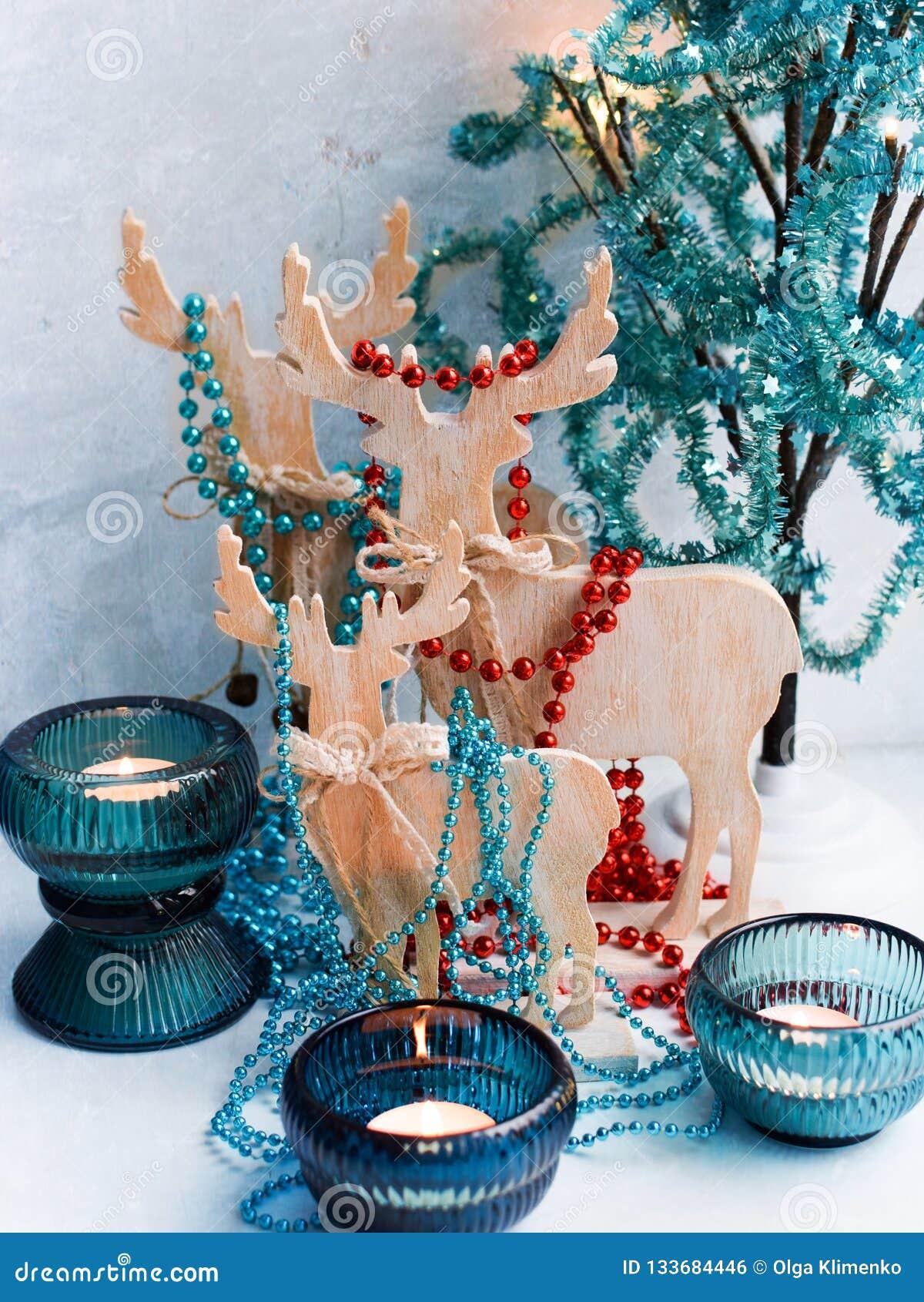 Drie houten die herten in de vorm van een familie, met slingers wordt verfraaid, decoratieve boom met lichten in turkooise kleure