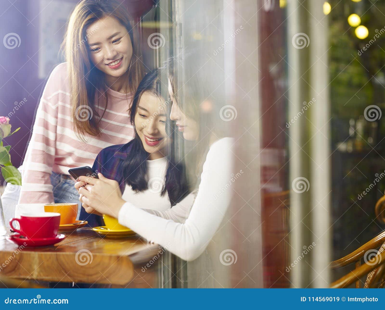 Drie jonge Aziatische vrouwen die mobiele telefoon in koffiewinkel bekijken