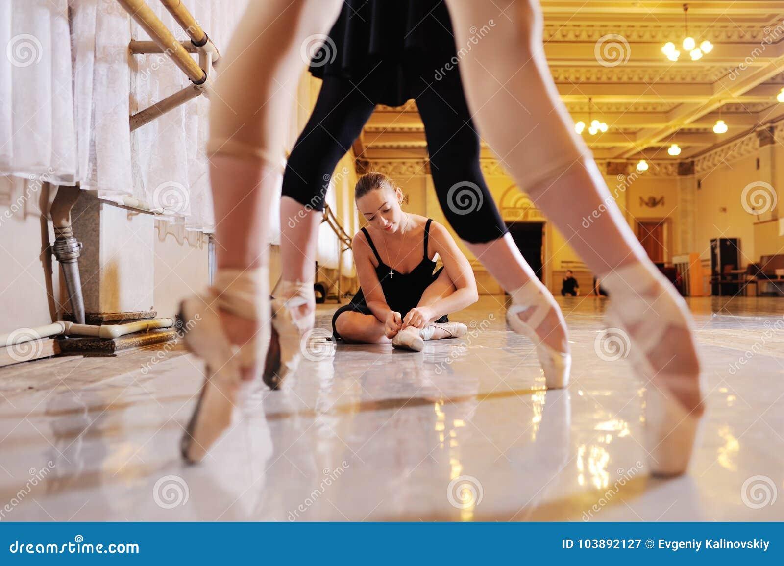 Drie jonge leuke ballerina s voeren oefeningen op een choregrafische machine of een staaf uit