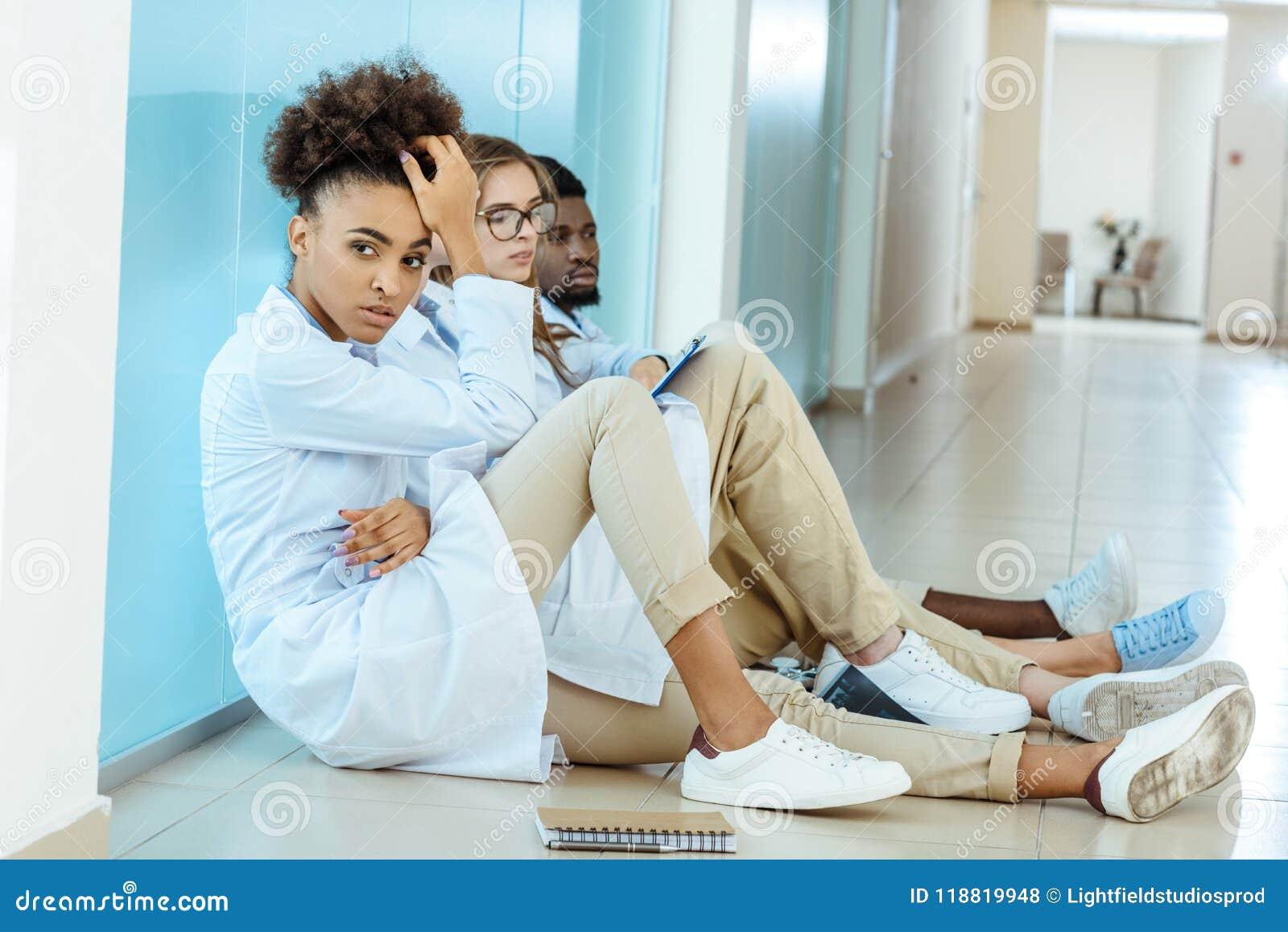 Drie jonge medische internen die in witte robes op een vloer zitten