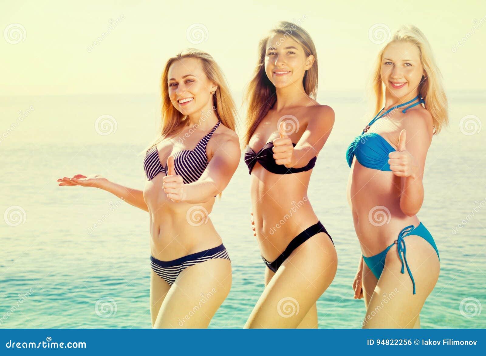 Drie jonge vrouwen in bikini op strand